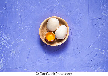 Easter eggs in a wooden dish on a purple background,