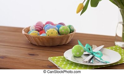 easter eggs in basket and flowers on served table - easter,...