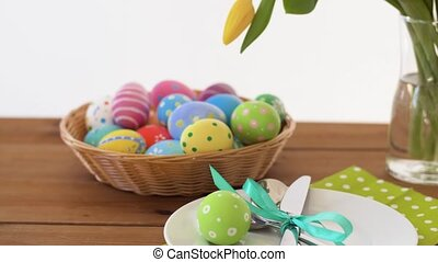 easter eggs in basket and flowers on served table
