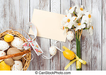 Easter eggs in basket, empty greeting card, bouquet of daffodils on wooden background. Easter decorations.