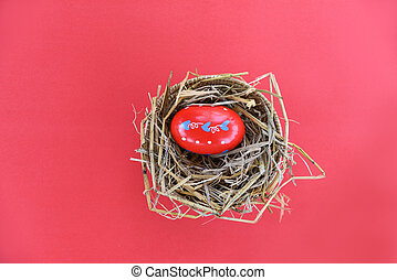 Easter eggs in basket nest decoration on red background - top view