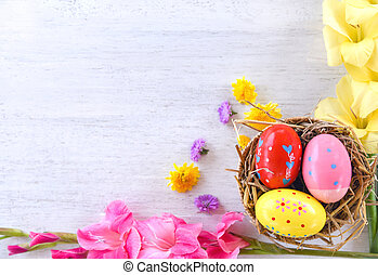 Easter eggs in basket nest decoration with colorful Gladiolus flowers on white background