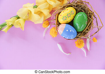 Easter eggs in basket nest decoration with gladiolus flower yellow on pink background