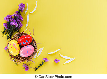 Easter eggs in basket nest decoration with purple flowers on yellow background - top view