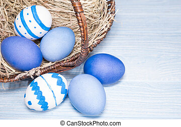 Easter eggs in basket on blue wooden background