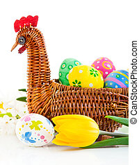 easter eggs in basket with yellow tulip flowers