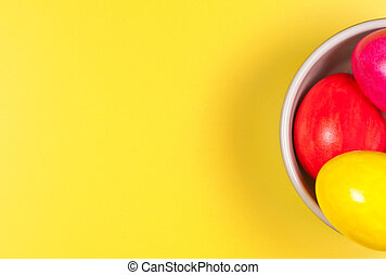 Easter eggs in bowl on yellow background.