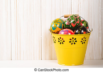 Easter eggs in bucket on white wooden background
