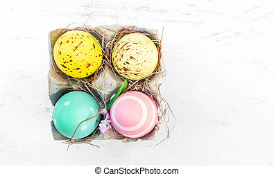 Easter eggs in egg cartoon box on white rustic wooden table ...