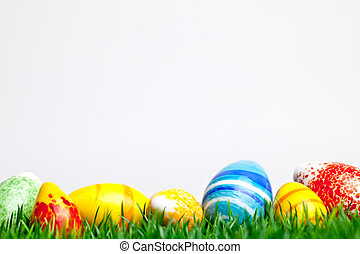 Easter eggs in green grass isolated on white background