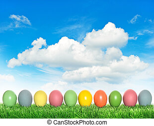 Easter eggs in green grass over cloudy blue sky