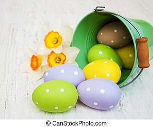 easter eggs in little buckets with daffodil flowers
