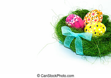 Easter eggs in nest from grass with a bow on white background