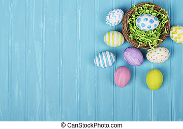 Easter eggs in nest on blue background