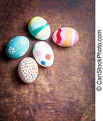 Easter eggs in nest on rustic wooden planks with copyspace. Happy Easter!