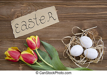 Easter eggs in nest on wooden background