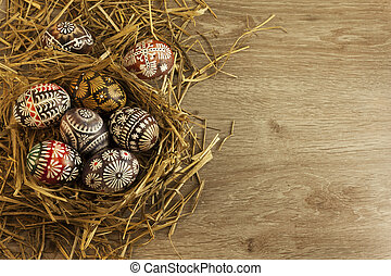Easter eggs in nest on wooden background