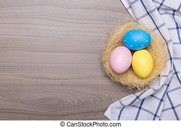 Easter eggs in the basket on wooden background