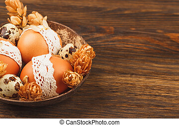 Easter eggs in the bowl, wooden background