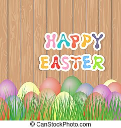 Easter eggs in the grass on a wooden background.