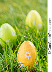 Easter eggs in the grass - Green yellow and orange easter...