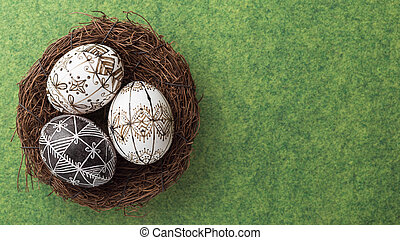 Easter eggs in the nest on green background