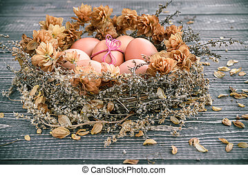Easter eggs in the nest on rustic wooden backgroun
