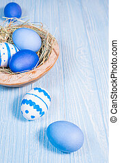 Easter eggs in wooden bowl on blue wooden background