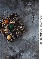 Easter eggs in wooden box on slate background