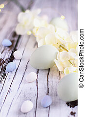 Easter Eggs malt candy eggs and Flowers against Wood Background