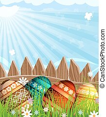 Easter eggs near a wooden fence in the meadow