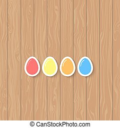 Easter eggs of different colors on a wooden background.