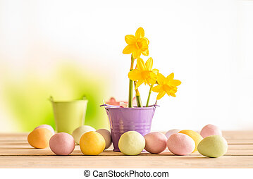 Easter eggs on a table with daffodils