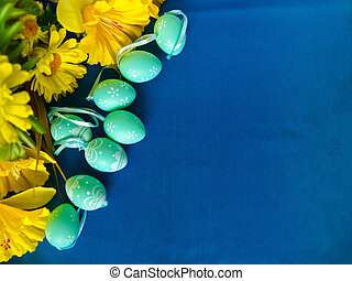 Easter eggs on blue silk, with yellow flowers.