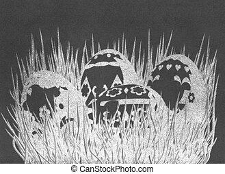 Easter eggs on grass on blackboard