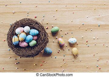 Easter eggs on on wood background top view with natural light. Flat lay style.