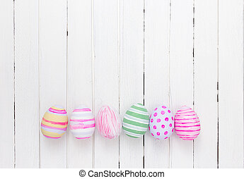 Easter eggs painted in pastel colors on a white wood...