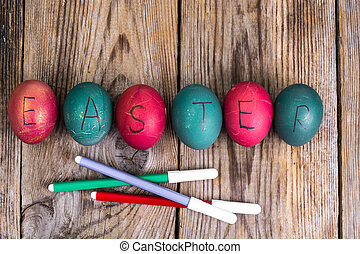 Easter eggs painted on white plate on wooden background