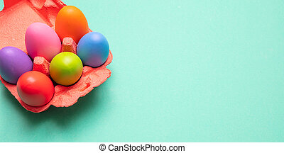 Easter eggs, pastel colors painted in a carton case, green background, banner