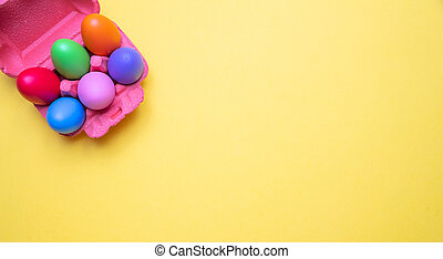Easter eggs, pastel colors painted in a carton case, yellow background