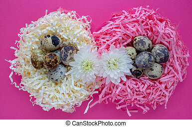 Easter eggs. Quail eggs in a decorative nest on a pink background. Copy space. The concept of Easter celebration