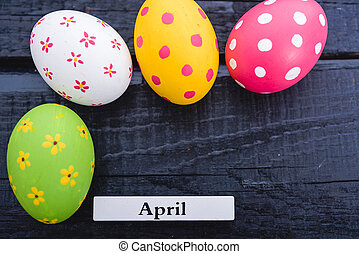 Easter eggs top view on black wooden background