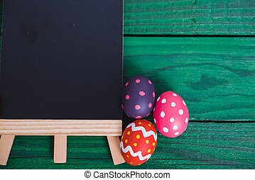 Easter eggs top view on green wooden background