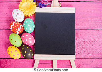 Easter eggs top view on pink wooden background