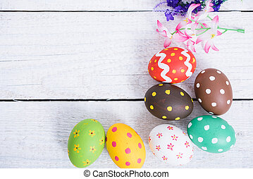 Easter eggs top view on white wooden background