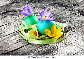 easter eggs with crocuses on wood background