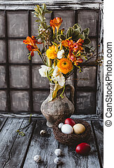 Easter eggs with spring flowers in jug on table