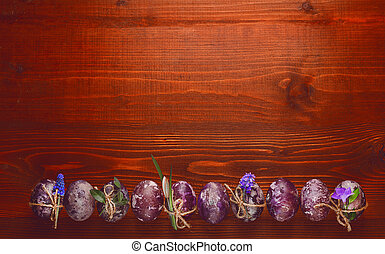 Easter eggs with spring flowers on a wooden background
