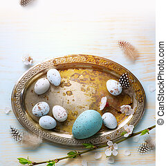 Easter Eggs with Spring Flowers on White Wooden Background