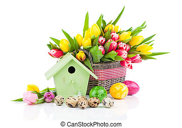 Easter eggs with tulips flowers and birdhouse, on a white background